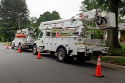 Rear and side view of parked communication utility trucks in residential neighborhood. Horizontal.