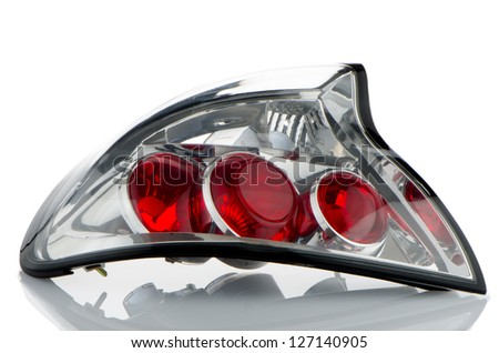 Rear automobile lamp detail on white reflective background.