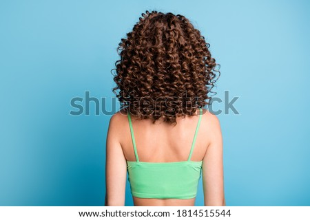 Rear back photo of young lady stand big extensive volume hairstyle nice curls sporty athletic trained spine back after exercises wear green crop top isolated blue color background ストックフォト ©