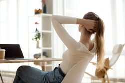 Rear back view at relaxed young woman resting finished work sitting at desk stretching with hands behind head taking peaceful break for relaxation feeling stress relief breathing air doing exercises