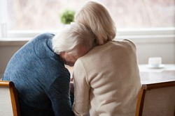 Rear back view at senior retired grey haired man leaning on shoulder of mature loving woman crying or laughing, older middle aged couple bonding, trust, support and understanding in marriage concept