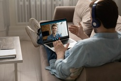 Rear back view relaxed young guy wearing headphones lying on cozy couch, enjoying fun talk with male buddy, sharing life news online using laptop video call application, distant communication concept.