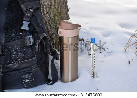 rear backpack next golden metal thermos with drink on halt in winter hike under the tree trunk and Mercury thermometer in the snow showing negative temperature Celsius. Close up