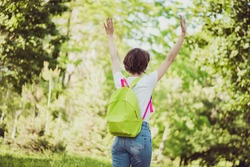 Rear behind profile view photo of pretty cute lady school backpack shoulders walk empty deserted park raise arms enjoy loneliness no people city crowd wear t-shirt green road outdoors