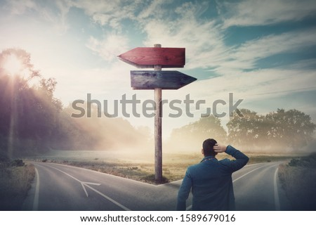 Rear businessman in front of crossroad and signpost arrows shows two different courses, left and right direction to choose. Road splits in distinct direction ways. Difficult decision, choice concept.
