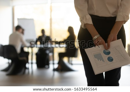 Rear close up view businesswoman holds financial stats papers behind back wait for performance speech feels nervous. Confident ceo ready to presentation on background clients sit at desk in boardroom