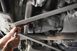 Rear differential fluid change in garage service shop.