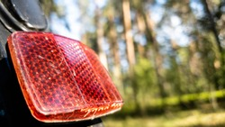 Rear light reflector on a red bicycle in the close up