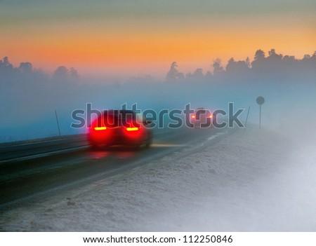 Rear lights of car on road in dark foggy winter evening