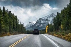 Rear of car driving on highway in the forest with mountain on gloomy at Banff national park
