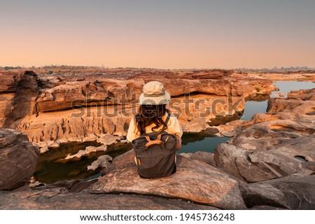 Rear of explorer woman sitting on natural rock canyon at evening in Sam Phan Bok of grand canyon at Thailand Zdjęcia stock ©