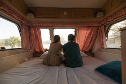 Rear of young couple sitting and taking a view on mattress inside of camper van