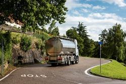 Rear quarter view of a fresh milk tanker truck in mountain, Italian Alps, Veneto, Italy, Europe.