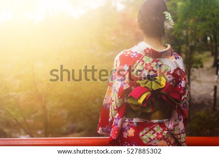 Rear shot of beautiful Japanese girl with traditional red floral pattern kimono dress enjoy autumn foliage colors during sunset with mist at Fushimi Inari temple garden, Kyoto, Japan. #527885302