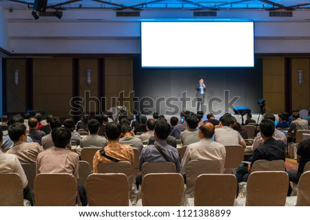 Rear side of Audiences sitting and listening the speackers on the stage in low light conference hall, event and seminar concept #1121388899