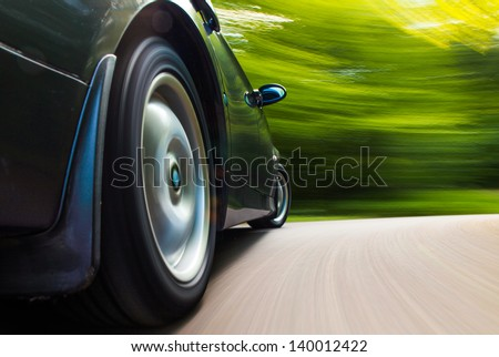 Rear side view of black car in turn with heavy blurred motion