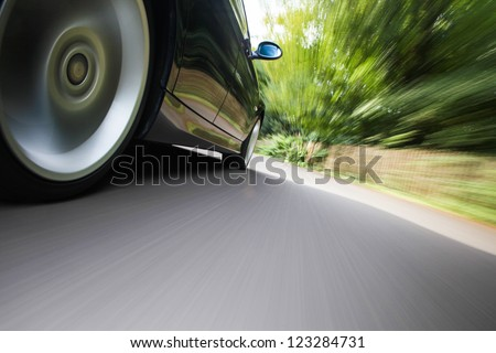 Rear side view of black family car driving fast on forest road #123284731
