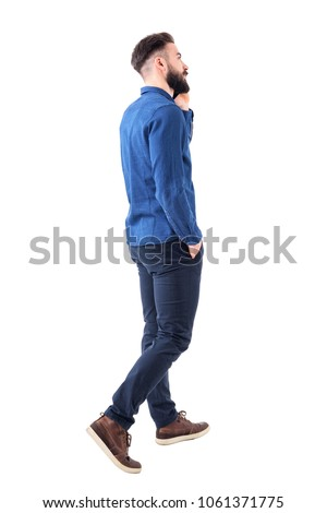 Rear side view of young elegant smart casual business man talking on the phone walking and looking up. Full body isolated on white background. #1061371775