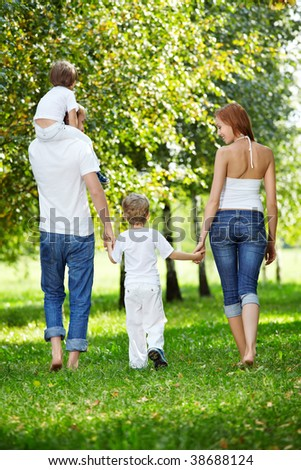 Rear view - a family with two children walks in park