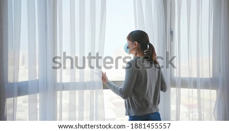 rear view asian young woman wearing face mask stay isolation at home for self quarantine due to epidemic of COVID19 - she looks out the window Stock photo ©