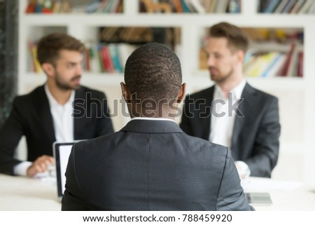 Rear view at african businessman against two caucasian men wearing suits, black vacancy candidate sitting his back to camera on job interview with two employers, hr, colleagues or recruiters concept