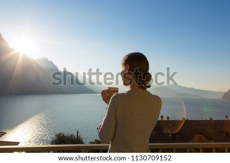 Rear view at happy free woman enjoying beautiful serene morning looking at sea lake and mountains nature landscape scenery starting new day drinking coffee relaxing. Italy, Lombardia, Riva di Solto