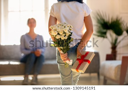 Rear view at little kid daughter holding flowers and gift box behind back congratulating happy young mom with mothers day or birthday, child girl hiding bouquet present making surprise to mum at home