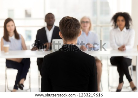 Rear view at man job seeker applicant during performance at interview with hr team, male vacancy candidate sits back talking making first impression on recruiters, human resources, employment concept