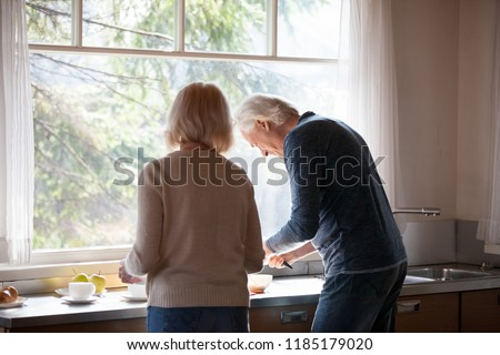 Rear view at middle aged loving couple preparing breakfast together in the kitchen standing at big window, caring mature husband helping senior wife to cook morning meal, old people at home lifestyle