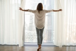 Rear view at rich woman standing looking out of full-length window of luxury modern apartment or hotel room opening curtains in the morning enjoying sunlight and city skyscrapers view feeling happy