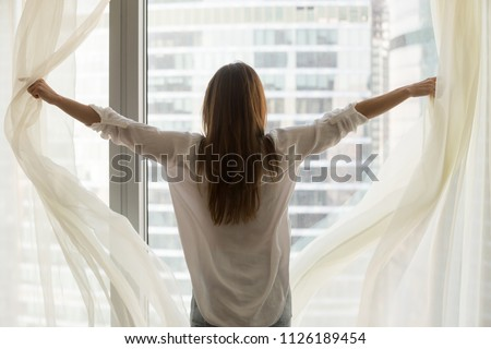 Rear view at rich woman traveler opening window curtains feeling happy free independent, enjoying starting new day, wellbeing, light good pleasant morning of luxury life and big city view concept