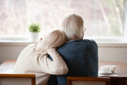 Rear view at senior grey haired loving caring family couple embracing relaxing at home together enjoying peaceful morning breakfast looking at window view thinking of future feeling calm nostalgic
