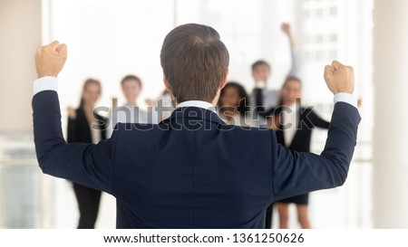 Rear view at successful company ceo celebrating business win victory success with corporate team in office, back of leader manager with hands raised overjoyed by work goal achievement reward growth