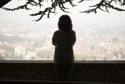 Rear view at thoughtful woman silhouette standing at view point looking at city watching urban cityscape vision pondering over question or problem, contemplating thinking of future loneliness concept