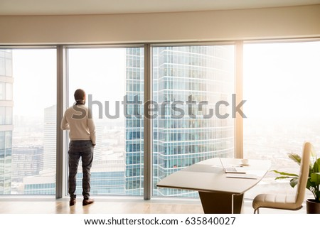 Rear view at young successful businessman standing in office looking through full-length window at cityscape with skyscrapers, dreaming or resting, waiting for meeting or considering business offer