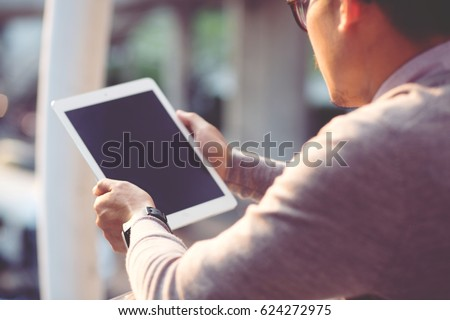 Rear view Business man using tablet #624272975