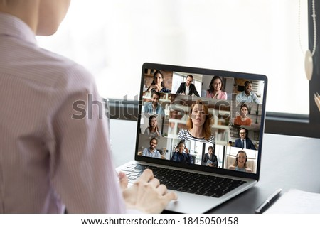 Rear view businesswoman executive engaged in conference with diverse colleagues, sitting at desk, multiracial business people on laptop screen, internet negotiations, online meeting, briefing