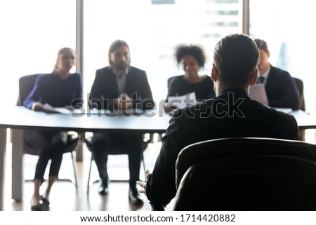Rear view candidate waiting for hr managers decision, interview result, sitting in front of four diverse recruiters in modern boardroom, male applicant applying for vacancy, employment concept