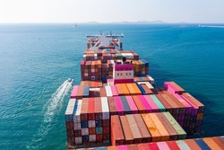 Rear view cargo container ship.  Business logistic transportation sea freight,Cargo ship, Cargo container in factory harbor at industrial estate for import export around in the world, Trade Port.