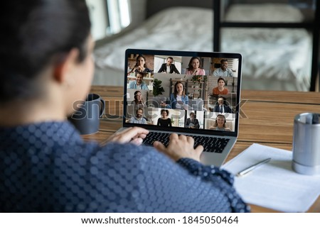 Rear view close up Indian businesswoman chatting with colleagues by video call, diverse business people on laptop screen, employees group discussing project, sharing ideas, online meeting, briefing