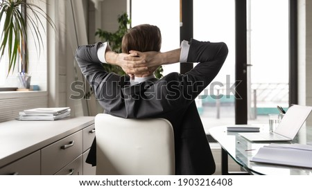 Rear view close up relaxed businessman stretching in comfortable office chair after work done, leaning back, successful confident executive manager leader boss daydreaming, visualizing good future Stock photo ©