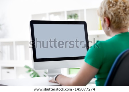 Rear view closeup of a young woman working of a computer