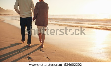Rear view cropped shot of a senior couple holding hands walking on the beach. Mature couple together taking a stroll on the sea shore at sunset.