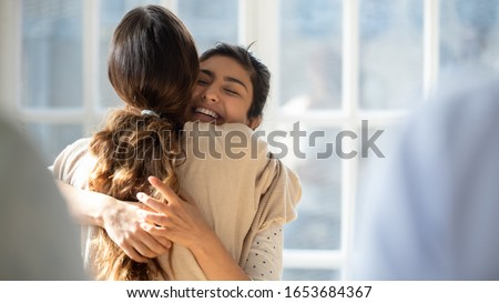 Rear view female cuddle Indian best friend glad to see each other enjoy tender moment show friendly relation and affection, woman psychologist counsellor hug girl supports her at group therapy session