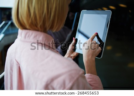 Rear view female person using digital tablet, business woman or freelancer working on touch pad in elevator, businesswoman using her wireless devices in modern office, young successful browsing on pad