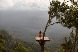 Rear view female tourist enjoying nature looking at the mountains and Agug volcano while standing on photo spot on the tree