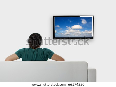 Rear view from a young man seated on the couch watching tv