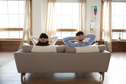 Rear view full length young couple relaxing on couch in modern apartment, young woman and man leaning back with hands behind head, resting, enjoying lazy weekend at home, moving day or mortgage