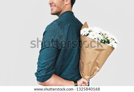 Rear view image of young happy man smiling hiding a bouquet of white flowers. Attractive male model with a bunch of flowers preparing for a date with girlfriend. Valentine's Day. Mother's Day concept