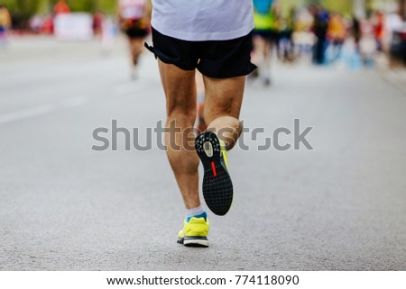 rear view legs male runner running in city marathon #774118090